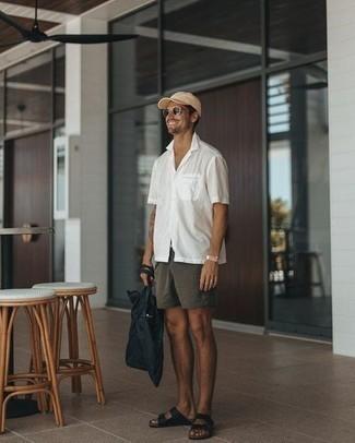Модные мужские луки 2020 фото в спортивном стиле: Белая рубашка с коротким рукавом и темно-серые брюки чинос — обязательные вещи в гардеробе парней с превосходным чувством стиля. Создать красивый контраст с остальными составляющими этого лука помогут черные кожаные сандалии.