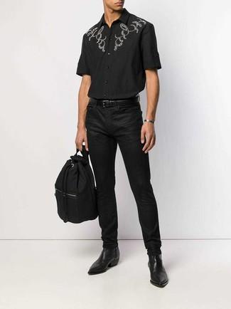 Как и с чем носить: черная рубашка с коротким рукавом с вышивкой, черные джинсы, черные кожаные ботинки челси, черный рюкзак из плотной ткани