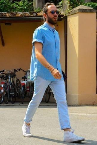 Голубые джинсы: с чем носить и как сочетать мужчине: Голубая рубашка с коротким рукавом из шамбре в паре с голубыми джинсами однозначно будет обращать на себя взоры прекрасных дам. Если сочетание несочетаемого привлекает тебя не меньше, чем безвременная классика, дополни этот ансамбль белыми высокими кедами из плотной ткани.