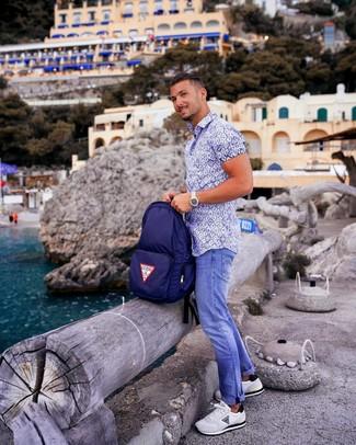 Как и с чем носить: бело-синяя рубашка с коротким рукавом с принтом, синие джинсы, белые кроссовки, темно-синий рюкзак из плотной ткани