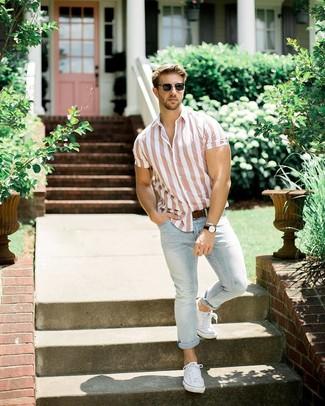 Модный лук: розовая рубашка с коротким рукавом в вертикальную полоску, голубые джинсы, белые низкие кеды из плотной ткани, темно-коричневый кожаный ремень