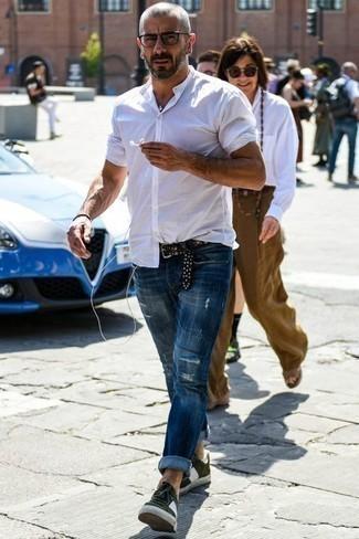 Оливковые замшевые низкие кеды: с чем носить и как сочетать мужчине: Если ты ценишь удобство и практичность, белая рубашка с коротким рукавом и синие рваные джинсы — классный выбор для модного повседневного мужского ансамбля. Оливковые замшевые низкие кеды добавят луку утонченности.