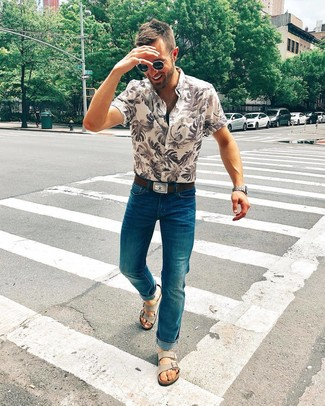 Как и с чем носить: бежевая рубашка с коротким рукавом с принтом, темно-бирюзовые джинсы, серые замшевые сандалии, темно-коричневый кожаный ремень