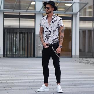 Как и с чем носить: белая рубашка с коротким рукавом с цветочным принтом, черные зауженные джинсы, белые кожаные низкие кеды, черная шерстяная шляпа