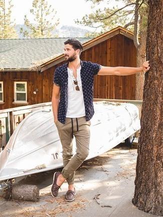 Модные мужские луки 2020 фото: Темно-синяя рубашка с коротким рукавом с принтом и светло-коричневые брюки чинос надежно закрепились в гардеробе многих парней, позволяя составлять незаезженные и стильные образы. В тандеме с этим ансамблем идеально выглядят коричневые кожаные топсайдеры.