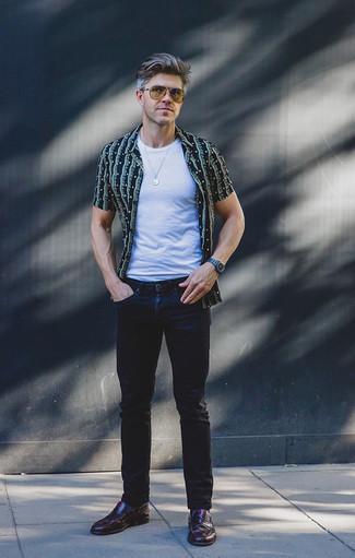 Темно-красные кожаные лоферы: с чем носить и как сочетать мужчине: Тандем темно-синей рубашки с коротким рукавом с принтом и темно-синих джинсов — замечательный пример современного стиля в большом городе. Не прочь сделать лук немного строже? Тогда в качестве обуви к этому ансамблю, обрати внимание на темно-красные кожаные лоферы.