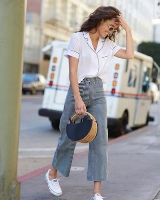 Белые низкие кеды из плотной ткани: с чем носить и как сочетать женщине: Белая рубашка с коротким рукавом и темно-сине-белые широкие брюки в вертикальную полоску — обязательные вещи в гардеробе женщин с отменным чувством стиля. Завершив образ белыми низкими кедами из плотной ткани, можно привнести в него немного легкомысленности.