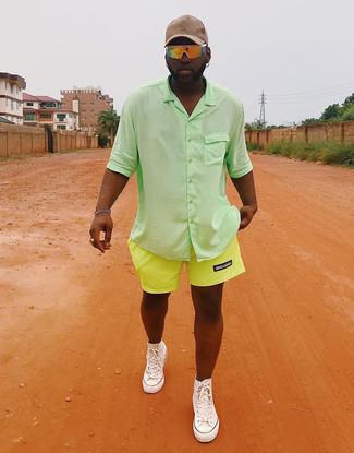 Как и с чем носить: зеленая рубашка с коротким рукавом, зелено-желтые шорты, белые высокие кеды из плотной ткани, бежевая бейсболка