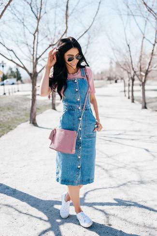 Как и с чем носить: синий джинсовый сарафан, розовая футболка с круглым вырезом, белые низкие кеды из плотной ткани, розовая кожаная сумка через плечо