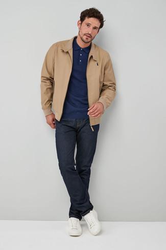 Как и с чем носить: светло-коричневая куртка харрингтон, темно-синий свитер с воротником поло, темно-синие джинсы, белые кожаные низкие кеды