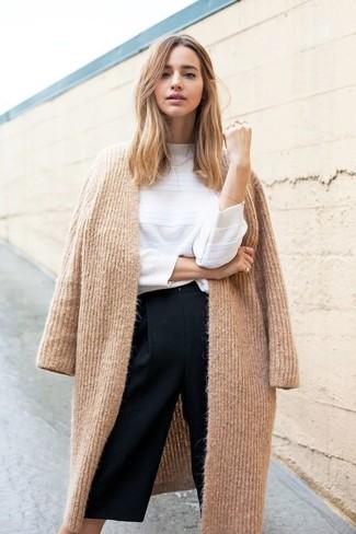 Как и с чем носить: светло-коричневое вязаное пальто, белый свитер с круглым вырезом, черные брюки-кюлоты