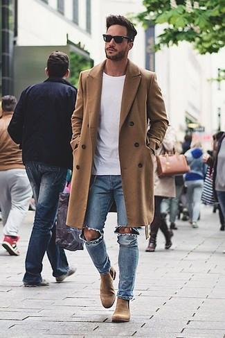 Длинное пальто и голубые рваные джинсы — необходимые вещи в гардеробе мужчины с чувством стиля. Чтобы немного разнообразить образ и сделать его элегантнее, можно надеть светло-коричневые замшевые ботинки челси.