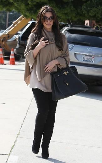 Как Kim Kardashian носит Светло-коричневое пончо, Черные джинсы скинни, Черные замшевые полусапоги, Черная кожаная большая сумка
