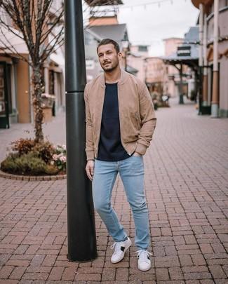 Как и с чем носить: светло-коричневый замшевый бомбер, темно-синий свитер с круглым вырезом, голубые джинсы, белые низкие кеды