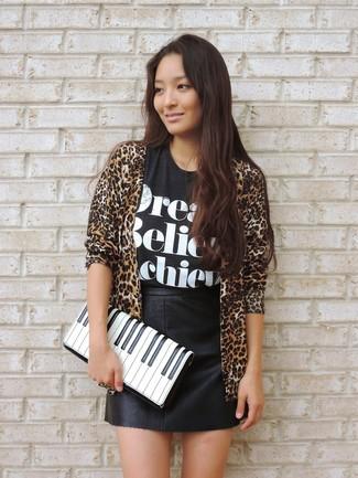Как и с чем носить: светло-коричневый открытый кардиган с леопардовым принтом, черно-белая футболка с круглым вырезом с принтом, черная кожаная мини-юбка, бело-черный кожаный клатч с принтом