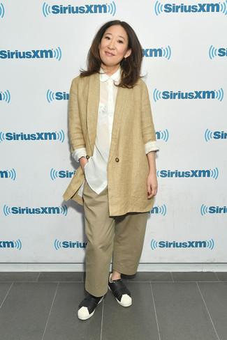 Как и с чем носить: светло-коричневый пиджак, белая шелковая классическая рубашка, светло-коричневые широкие брюки, черно-белые кожаные низкие кеды