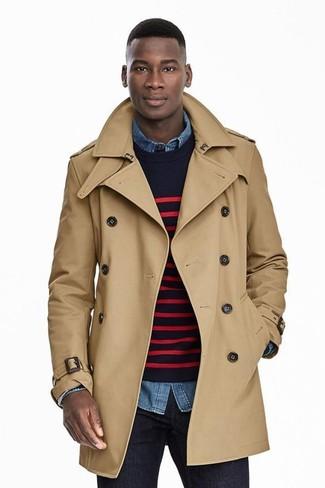 Модный лук: светло-коричневый плащ, темно-сине-красный свитер с круглым вырезом в горизонтальную полоску, синяя джинсовая рубашка, темно-синие джинсы
