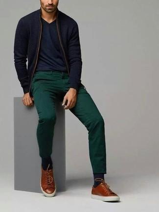 Модные мужские луки 2020 фото: Темно-синий свитер на молнии и темно-зеленые брюки чинос — must have элементы в гардеробе молодых людей с чувством стиля. Коричневые кожаные низкие кеды подарят удобство в движении.