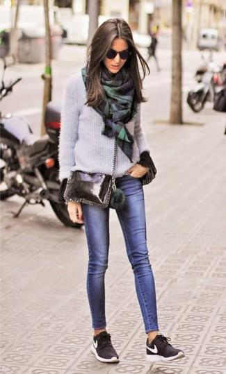 Как и с чем носить: серый свитер с круглым вырезом, черная блузка с длинным рукавом с рюшами, темно-синие джинсы скинни, черные кроссовки