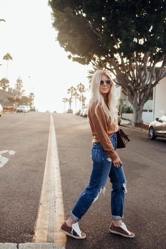 Женские луки в спортивном стиле: Коричневый свитер с круглым вырезом и синие рваные джинсы-бойфренды — выбор дамского пола, которые никогда не сидят на месте. И почему бы не привнести в этот лук на каждый день немного изысканности с помощью коричневых замшевых низких кед?