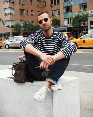 Как и с чем носить: темно-сине-белый свитер с круглым вырезом в горизонтальную полоску, темно-синие джинсы, белые низкие кеды из плотной ткани, темно-коричневая кожаная сумка почтальона
