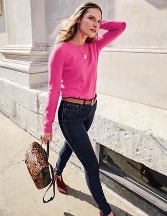 Как и с чем носить: ярко-розовый свитер с круглым вырезом, темно-синие джинсы скинни, темно-красные замшевые ботильоны, темно-коричневый кожаный рюкзак с леопардовым принтом