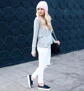 Как и с чем носить: серый свитер с круглым вырезом с рюшами, белые рваные джинсы скинни, черные кожаные слипоны, черная кожаная сумка через плечо