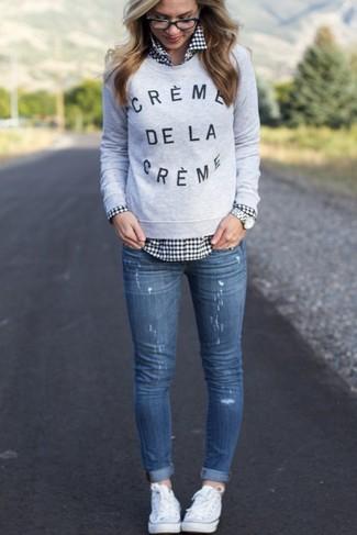 Серый свитер с круглым вырезом с принтом и синие рваные джинсы скинни — универсальное сочетание и для вечернего свидания с молодым человеком в кино или кафе, и для похода в музей. Выбирая обувь, можно немного побаловаться и завершить образ белыми низкими кедами.