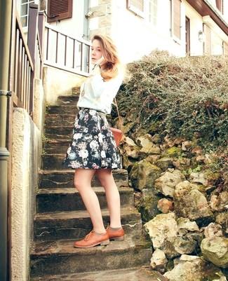Если ты любишь выглядеть красиво и при этом чувствовать себя комфортно и расслабленно, примерь это сочетание голубого свитера с круглым вырезом и черной короткой юбки-солнце с цветочным принтом. Табачные кожаные оксфорды добавят чуточку классики в твой лук.