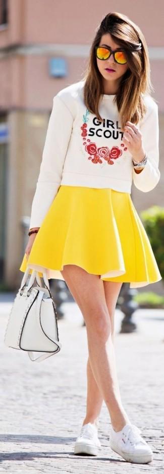 Как и с чем носить: белый свитер с круглым вырезом с принтом, желтая короткая юбка-солнце, белые плимсоллы, белая кожаная сумка-саквояж