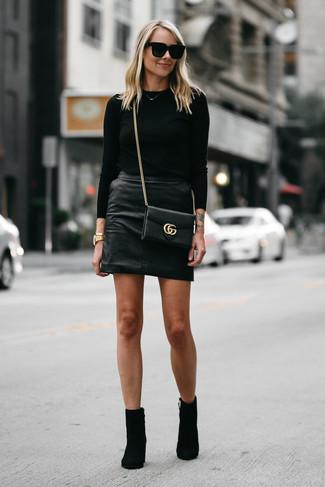 Как и с чем носить: черный свитер с круглым вырезом, черная кожаная мини-юбка, черные замшевые ботильоны, черная кожаная сумка через плечо