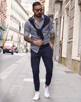 Как и с чем носить: темно-синий свитер с круглым вырезом, темно-сине-белая рубашка с длинным рукавом с цветочным принтом, темно-синие брюки чинос, белые кожаные низкие кеды