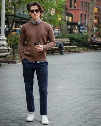 Модные мужские луки 2020 фото: Сочетание коричневого свитера с круглым вырезом и темно-синих брюк чинос смотрится мужественно и по моде. Ты можешь легко приспособить такой образ к повседневным нуждам, надев белыми кожаными низкими кедами.