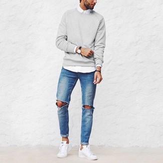 Серый свитер с круглым вырезом и синие рваные джинсы — отличный вариант непринужденного повседневного лука. Что касается обуви, неплохо дополнят образ белые низкие кеды.