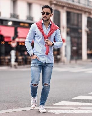 Как и с чем носить: ярко-розовый свитер с круглым вырезом, голубая рубашка с длинным рукавом в вертикальную полоску, синие рваные зауженные джинсы, белые низкие кеды из плотной ткани