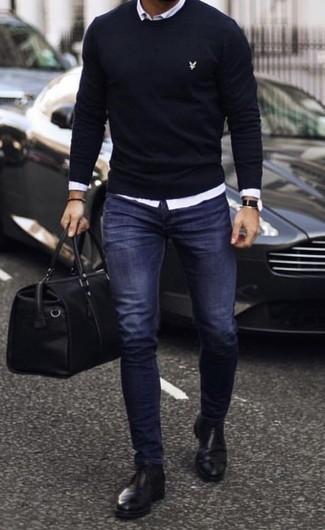 Темно-синие зауженные джинсы: с чем носить и как сочетать мужчине: Темно-синий свитер с круглым вырезом и темно-синие зауженные джинсы — обязательные вещи в арсенале современного джентльмена. Разбавить образ и добавить в него чуточку классики помогут черные кожаные ботинки челси.