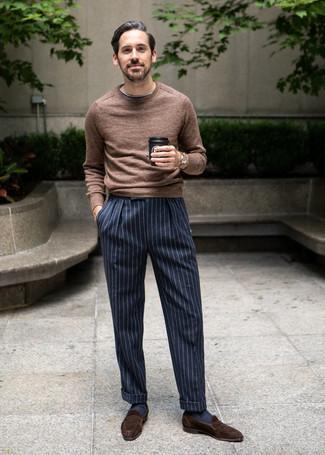 Темно-коричневые замшевые лоферы: с чем носить и как сочетать мужчине: Коричневый свитер с круглым вырезом в сочетании с темно-сине-белыми классическими брюками в вертикальную полоску подойдет для свидания или похода в бар с коллегами. Этот образ обретет свежее прочтение в сочетании с темно-коричневыми замшевыми лоферами.