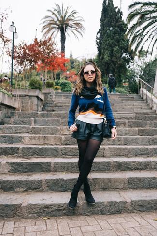 Как и с чем носить: синий свитер с круглым вырезом с принтом, черные кожаные шорты, черные замшевые ботильоны, черная кожаная сумка через плечо