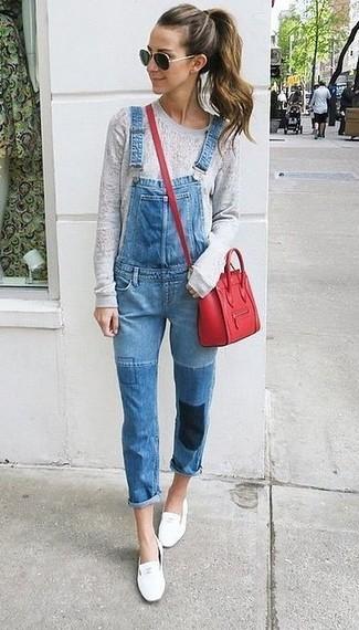 Как и с чем носить: серый свитер с круглым вырезом, синие джинсовые штаны-комбинезон, белые кожаные лоферы, красная кожаная сумка через плечо