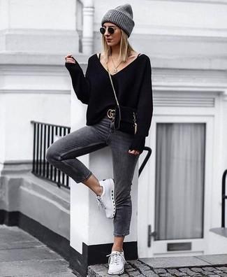 Как и с чем носить: черный свитер с v-образным вырезом, темно-серые джинсы скинни, белые низкие кеды, черная замшевая сумка через плечо