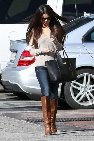 Как Selena Gomez носит Серый свитер с v-образным вырезом, Темно-синие джинсы скинни, Коричневые кожаные сапоги, Черная кожаная большая сумка
