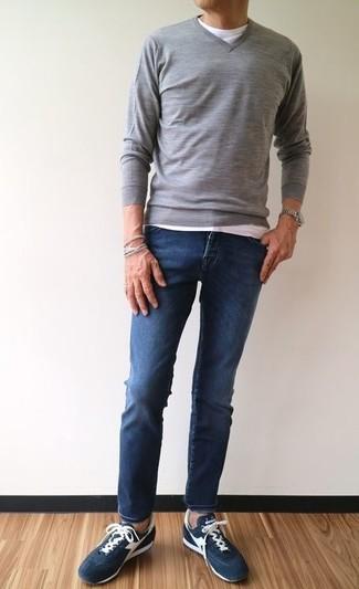 Как и с чем носить: серый свитер с v-образным вырезом, белая футболка с круглым вырезом, темно-синие зауженные джинсы, темно-синие замшевые низкие кеды