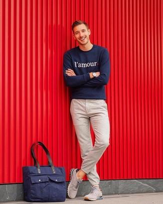 Как и с чем носить: темно-синий свитшот с принтом, бежевые шерстяные брюки чинос, серые замшевые кроссовки, темно-синяя большая сумка из плотной ткани