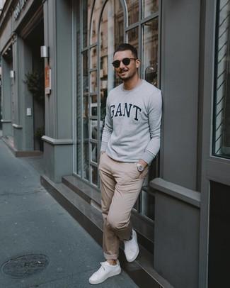 Как и с чем носить: серый свитшот с принтом, бежевые брюки чинос, белые кожаные низкие кеды, черные солнцезащитные очки