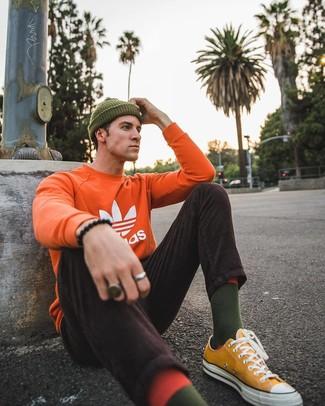 Как и с чем носить: оранжевый свитшот с принтом, темно-коричневые вельветовые джинсы, горчичные низкие кеды из плотной ткани, оливковая шапка