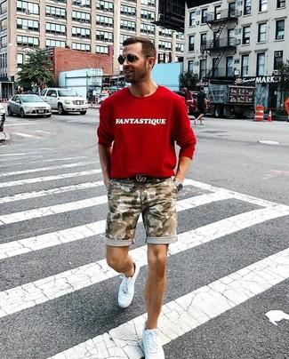 Как и с чем носить: красный свитшот с принтом, оливковые шорты с камуфляжным принтом, белые кожаные низкие кеды, черный кожаный ремень