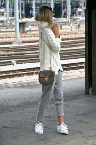 Как и с чем носить: белый вязаный свободный свитер, серые брюки-галифе, белые низкие кеды, оливковая кожаная сумка через плечо