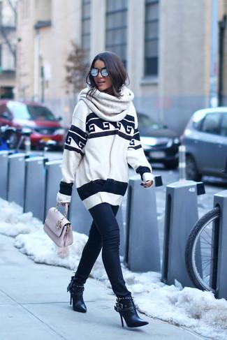Как и с чем носить: бело-черный свободный свитер с принтом, черные джинсы скинни, черные кожаные ботильоны, розовая кожаная сумка-саквояж