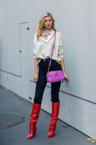 Как и с чем носить: серый свободный свитер, черные джинсы скинни, красные кожаные сапоги, пурпурная кожаная сумка через плечо
