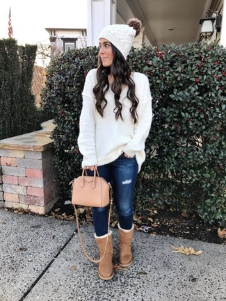 Как и с чем носить: белый вязаный свободный свитер, темно-синие рваные джинсы скинни, светло-коричневые угги, розовая кожаная большая сумка